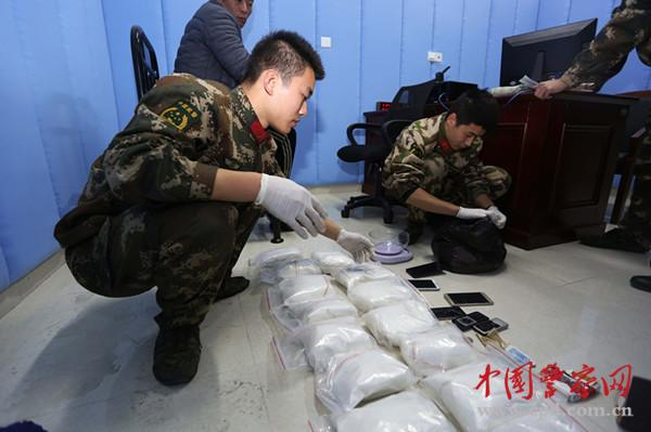 People_s_Armed_Police_look_over_packages_of_drugs_siezed_from_a_smuggler__in_february