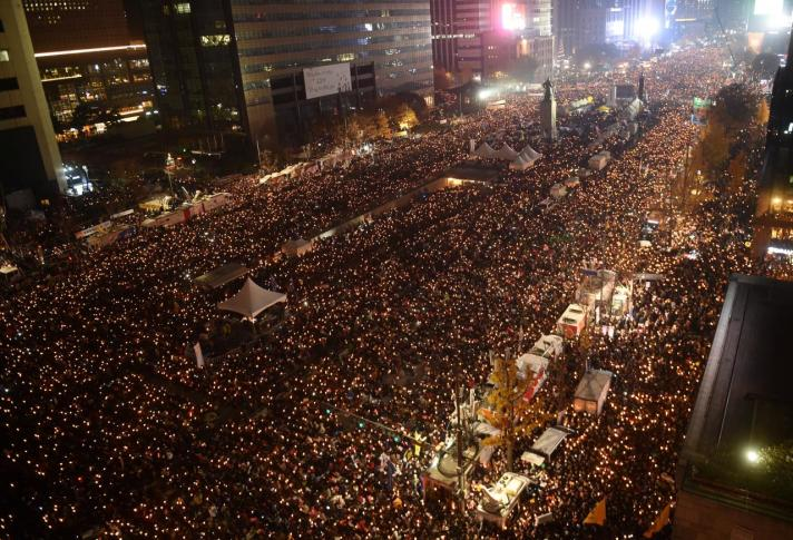 Protesters hold candles during an anti-government rally in central Seoul